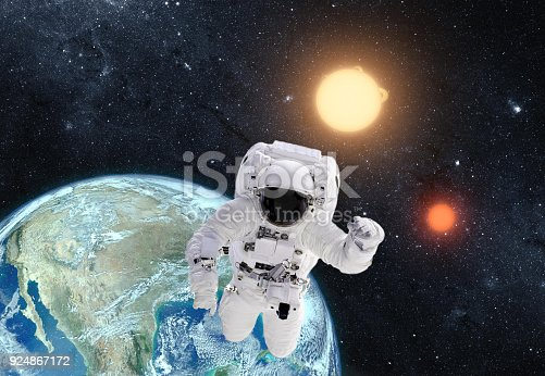 istock Astronaut in outer space over the planet earth. This image is a collage of different images furnished by NASA 924867172