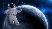 A composite image of an untethered astronaut in rear view, isolated and drifting off into deep space above the earth. This image uses a mixture of both CGI elements for the spaceman, and public domain NASA imagery for the earth and moon. The astronaut is wearing a generic space suit.