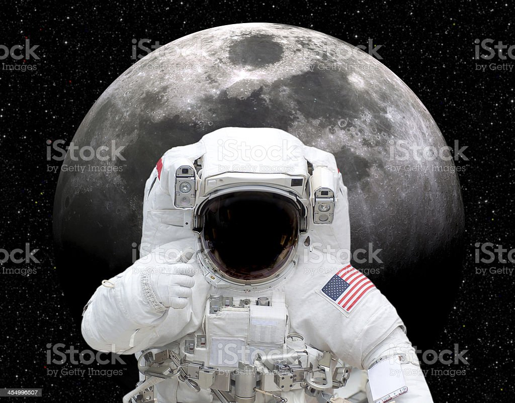 Astronaut in space giving thumbs up to moon stock photo