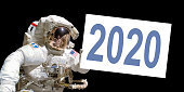 Astronaut in space holding a 2020 white  board - New year greeting card - elements of this image are provided by NASA