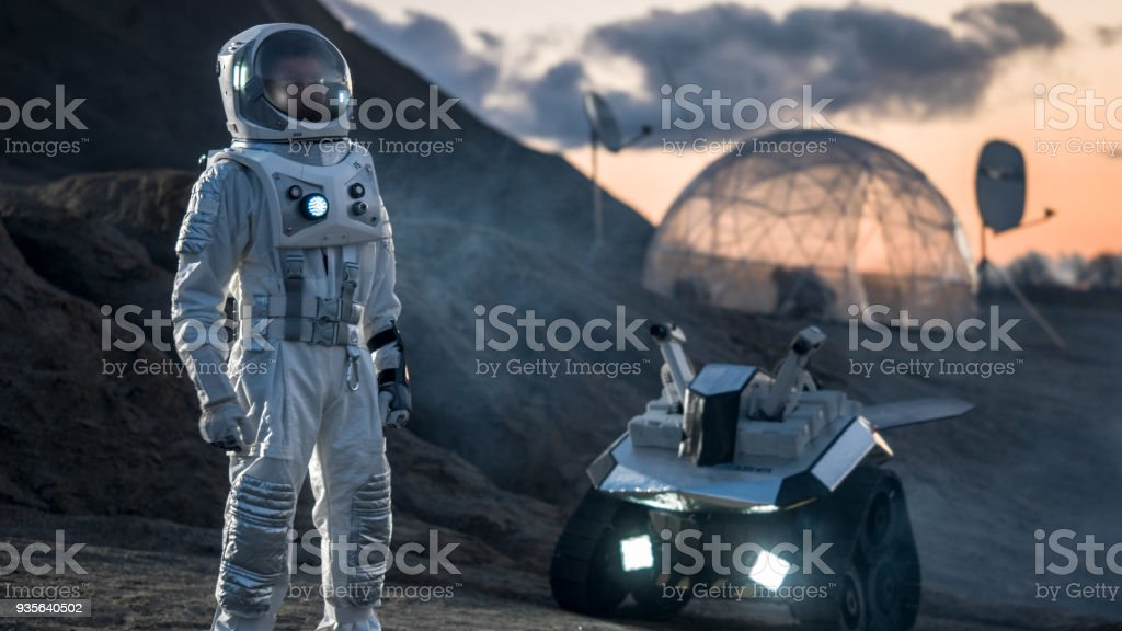 Astronaut in Space Suit Confidently Standing on Alien Planet, Exploration of the the Planet's Surface. In the Background Research Base/ Station and Rover. Space Travel, Colonization Concept. stock photo