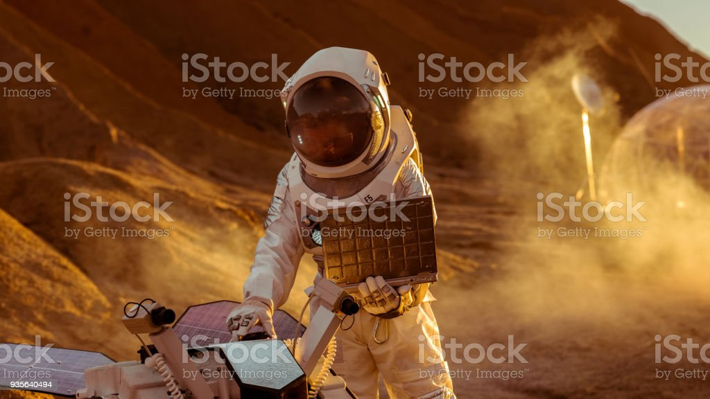 Astronaut in the Space Suit Works on Laptop, Adjusting Rover For Mars further Mars Exploration.Space Exploration Concept.First Manned Mission on Red Planet. stock photo
