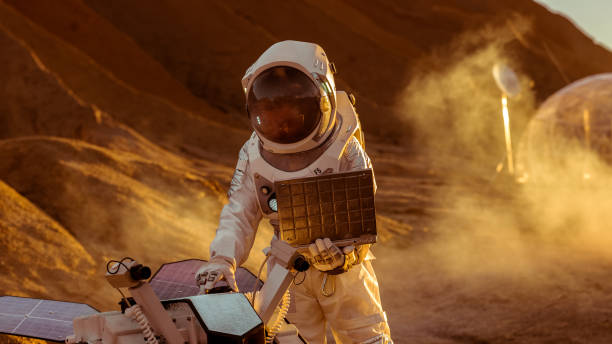 astronauten im raumanzug arbeiten am laptop, anpassung rover für weitere mars exploration.space exploration concept.first bemannte marsmission auf roten planeten. - erforschung des weltalls stock-fotos und bilder