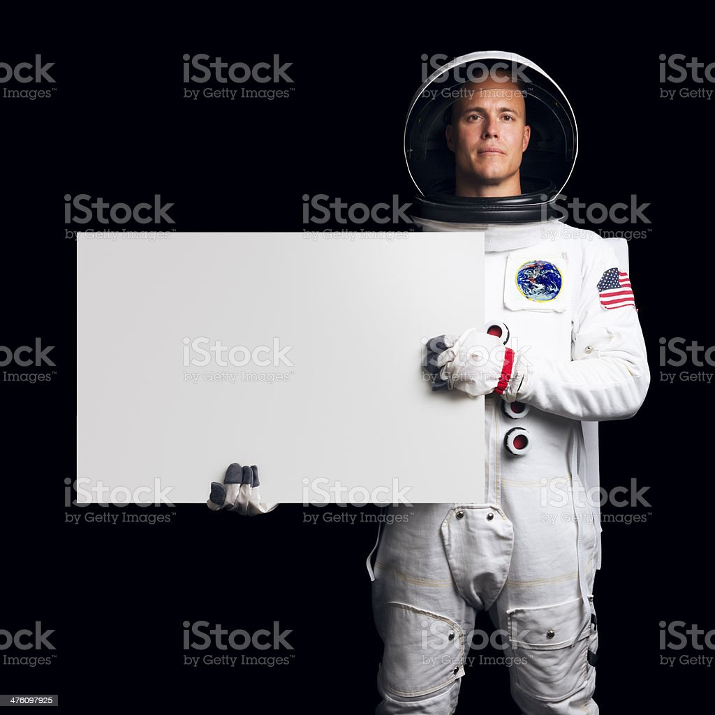 Astronaut Isolated on Black Holding a Blank Sign stock photo