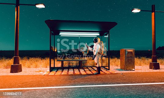 istock Astronaut looks a mobile phone while standing at a bus stop a night 1239934217