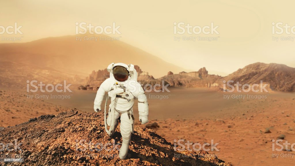 Astronaut man walks in the desert with mountains in Mars. Journey to the red planet. Landscape of the red planet Mars stock photo