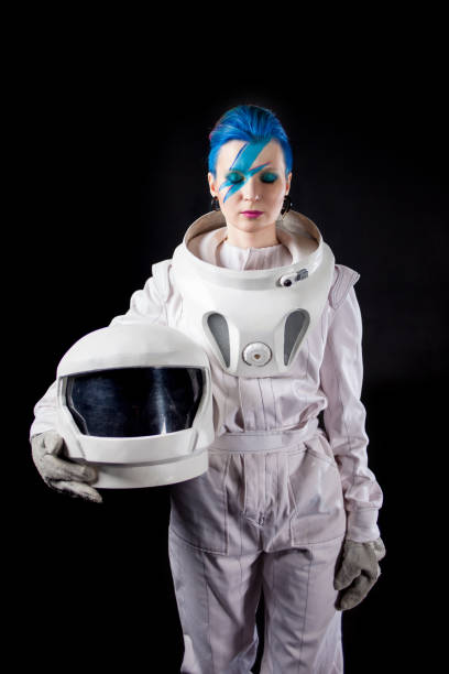 Astronaut on a black background, a young woman with face art in the space suit. Helmet in hands stock photo