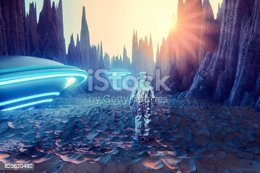 istock Astronaut on alien planet discovering glowing UFOs 825620492