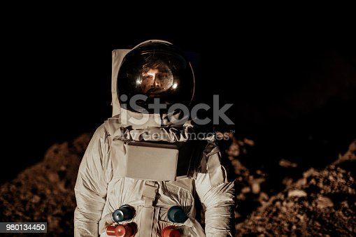 One man, astronaut exploring the land on the other planet alone at night.