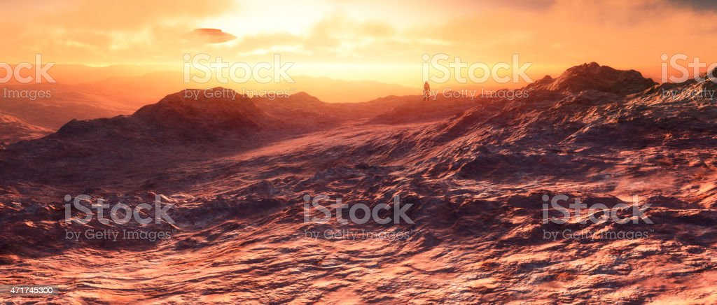 Astronaut on distant planet with UFOs in the sky stock photo