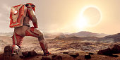 An astronaut kneeling on one leg and resting arm on thigh,  dressed in white and orange spacesuit and backpack on planet Mars. The spaceman is looking out over an empty barren rocky terrain on Mars, at a solar eclipse at sunset in contemplation.