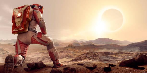 astronaut on mars kneeling and watching eclipse at sunset - esplorazione spaziale foto e immagini stock
