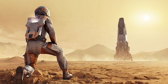 A close up image of an astronaut on Mars kneeling and looking at a rocket in the distance. The spaceman or spacewoman is dressed in full space suit viewed from behind, kneeling on rocks and looking into the distance where a space rocket is at rest on the flat terrain.