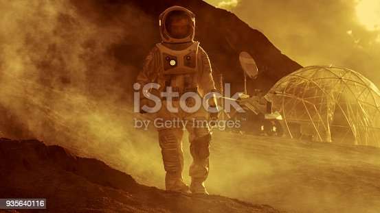 istock Astronaut on Mars Walking on the Exploring Expedition. In the Background His Base/ Research Station. First Manned Mission To Mars, Technological Advance Brings Space Exploration, Colonization. 935640116