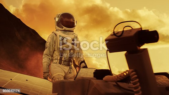 istock Astronaut on Mars Walking on the Exploring Expedition. In the Background His Base/ Research Station. First Manned Mission To Mars, Technological Advance Brings Space Exploration, Colonization. 935640174