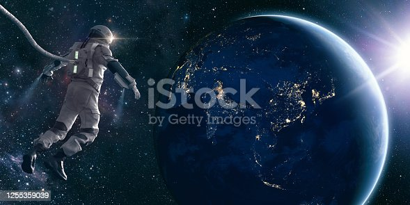 An CG astronaut in a modern space suit, connected to a tethered lifeline floats in deep space and looks at the lights of planet earth as the sun rises. Distant stars and galaxies are visible in the background. Credit: NASA https://earthobservatory.nasa.gov/images/79790/city-lights-of-asia-and-australiaand ESO for background images.
