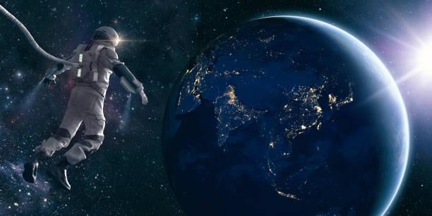 Astronaut On Space Walk Looks At Lights of Planet Earth An CG astronaut in a modern space suit, connected to a tethered lifeline floats in deep space and looks at the lights of planet earth as the sun rises. Distant stars and galaxies are visible in the background. Credit: NASA https://earthobservatory.nasa.gov/images/79790/city-lights-of-asia-and-australiaand ESO for background images. outer space stock pictures, royalty-free photos & images