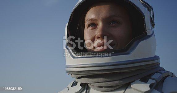 Medium shot of astronaut opening helmet and smiling