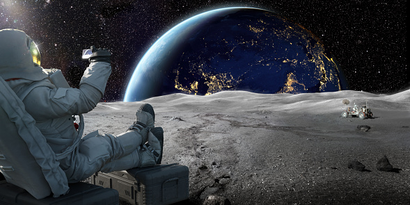 An astronaut sitting on a crate on the lunar surface, holding up a smartphone recording the sun as it starts to rise over the earth.   Credit: Earth image from NASA https://earthobservatory.nasa.gov/images/79790/city-lights-of-asia-and-australia