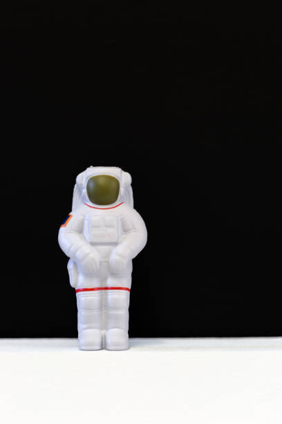 Astronaut soft toy on white floor and black background stock photo