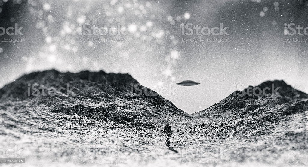 Astronaut walking towards UFO - foto de acervo