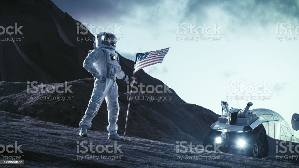 Astronaut Wearing Space Suit Plants American Flag on the Alien Planet. Patriotic and Proud Moment for the Whole of Humanity. Space Travel and Colonization Concept. stock photo