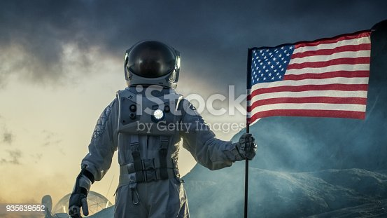 istock Astronaut Wearing Space Suit Plants American Flag on the Red Planet/ Mars. Patriotic and Proud Moment for the Whole of Humanity. Space Travel and Colonization Concept. 935639552