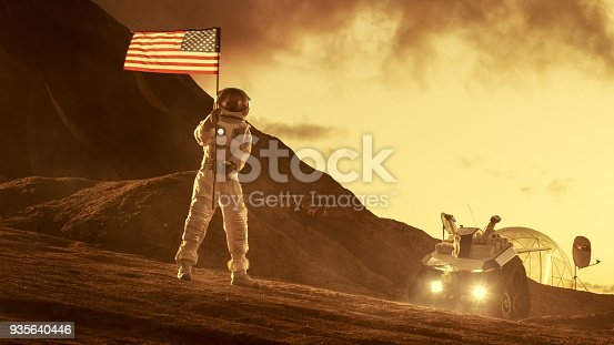 istock Astronaut Wearing Space Suit Plants American Flag on the Red Planet/ Mars. Patriotic and Proud Moment for the Whole of Humanity. Space Travel and Colonization Concept. 935640446