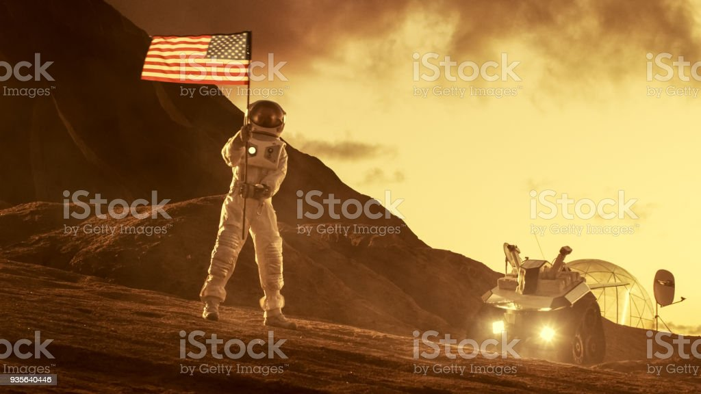 Astronaut Wearing Space Suit Plants American Flag on the Red Planet/ Mars. Patriotic and Proud Moment for the Whole of Humanity. Space Travel and Colonization Concept. stock photo
