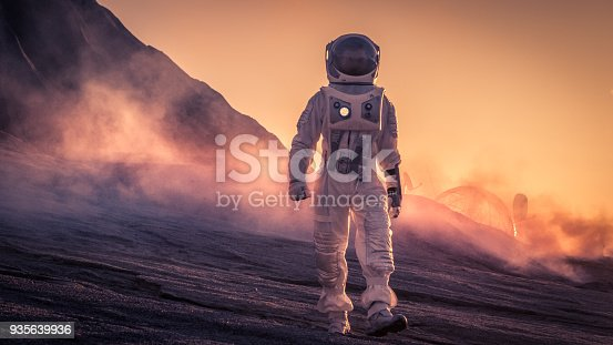 istock Astronaut Wearing Space Suit Walks on the Red Planet/Venus During Sunset. In the Background His Base with Rover Parked, Hot Red Daylight Sun Shines. 935639936