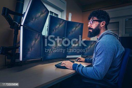Astronomer in control panel room multi screen sitting profile with beard