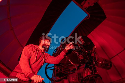 Astronomer in photo telescope dome with red light checking settings for the coming night