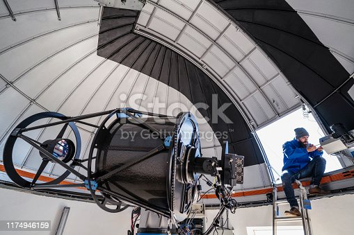 Astronomer technician in observatory telescope dome doing shutter maintenance tasks