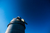 Rozhen astronomical observatory under the night sky stars. Blue sky with hundreds of stars of the Milky way.