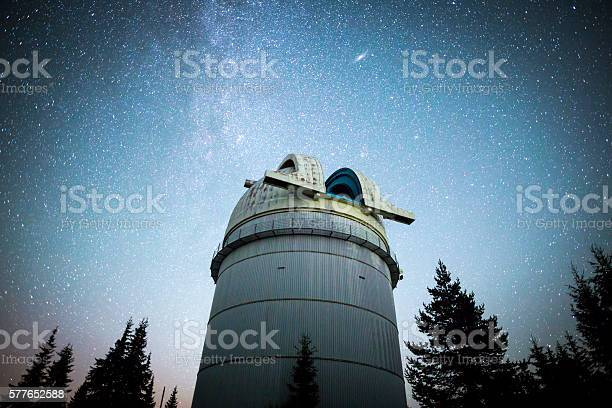 Photo of Astronomical Observatory under the night sky stars. Vignette