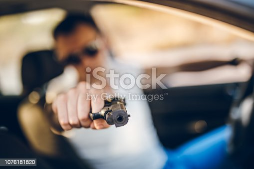 Tough man pointing gun while driving car