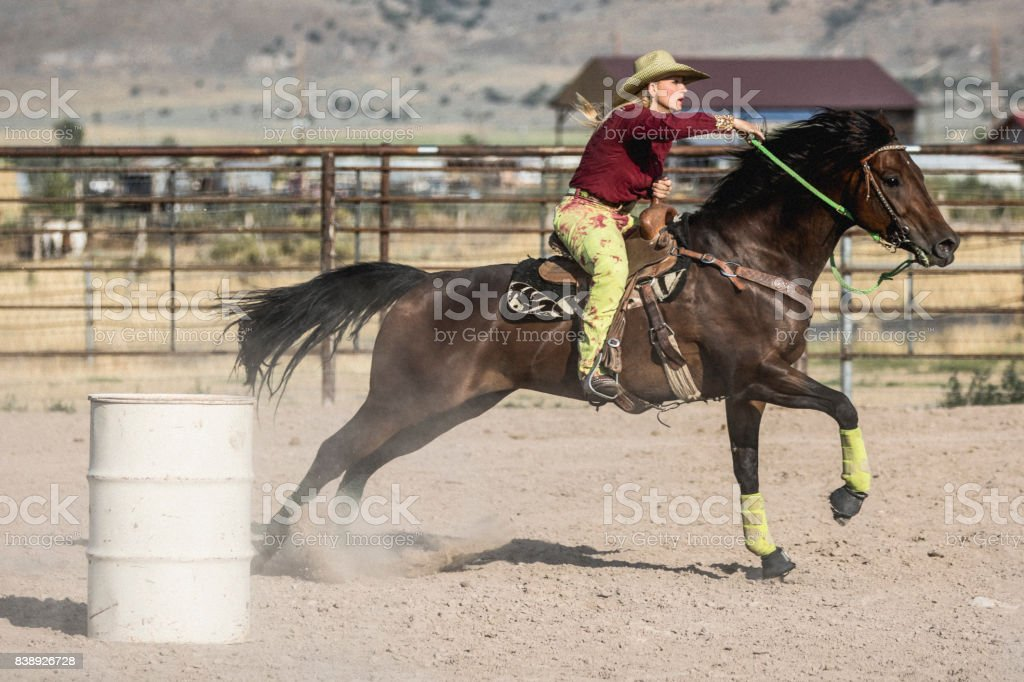At a rodeo, cowgirl on her horse aiming at completing a cloverleaf pattern during the barrel racing event, also called Gymkhana. stock photo