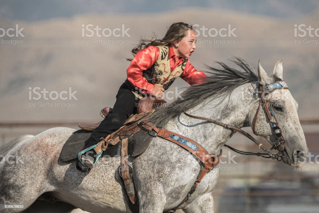 At a rodeo, very young cowgirl on her horse aiming at completing a cloverleaf pattern during the barrel racing event, also called Gymkhana. stock photo