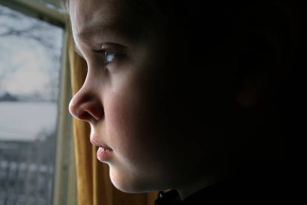 At a Window: Boy Stares Sadly Outside stock photo