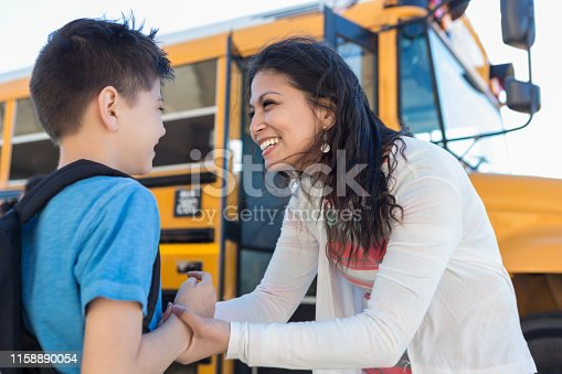 As they stand by the bus, the mid adult mom encourages her young son on the first day of school.