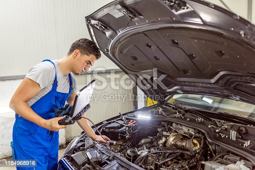 Mechanic using a laptop to work at the repair garage. Photo of Professional car mechanic working in auto repair service. Experienced car technician using a laptop, during car diagnostic at his workshop. Black hair male mechanic repairing modern SUV car at his garage, copy space. Technology, electronic concept.