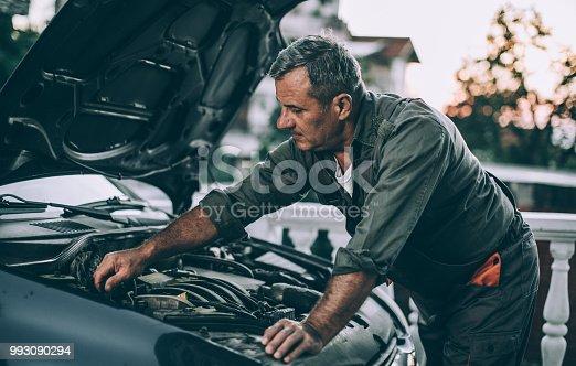 At car service.Senior repair his car