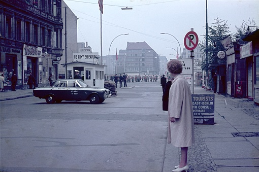 Berlin (West), Germany, 1962. American Sector of the Allied Forces. At the famous Checkpoint Charlie in the western Friedrichstraße. Also: Sentry, tourists, shops, military, police, sector border and buildings.