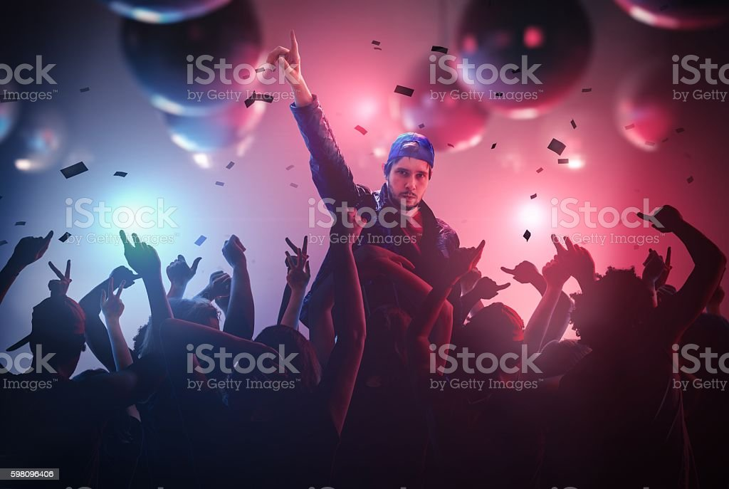 DJ at disco party in club with crowd of people. stock photo