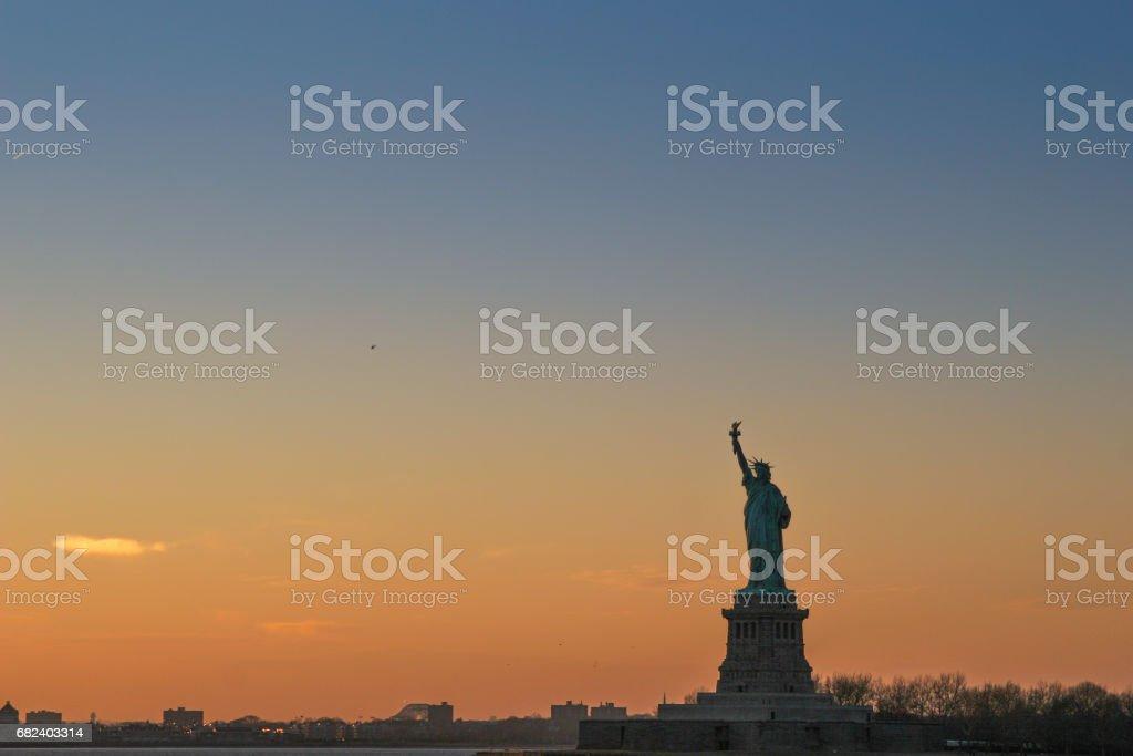 In der Abenddämmerung, die Freiheitsstatue auf Liberty Island im Hafen von New York. Lizenzfreies stock-foto