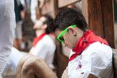Pamplona, Spain - July 13, 2013: Young man sleeping in anticipation of start of  race bulls on street Estafeta at San Fermin festival.