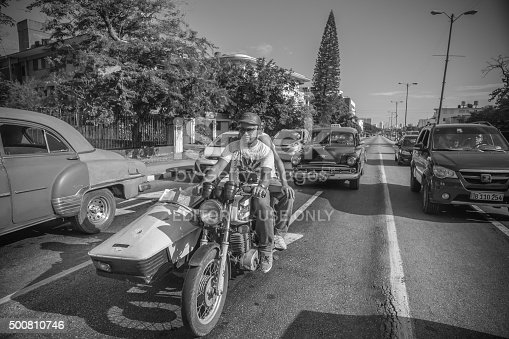 Havana, Cuba - November 7, 2015. Old Russian motorcycle with side cab on the stop light in Old Havana, Cuba. Diver looking ahead. Passengers on the back seat. In the background line of cars and bus waiting in traffic. Drivers of the cars looking out, waiting for a green light. This is one of countless vintage Russian made motorcycles and cars imported to Cuba before the Revolution but still running after more than 50 years due to ingenuity of Cuban car mechanics and some help of various old car parts, including the left over of Russian diesel engines. Most of these cars run across the city as TAXI for local Cubans.