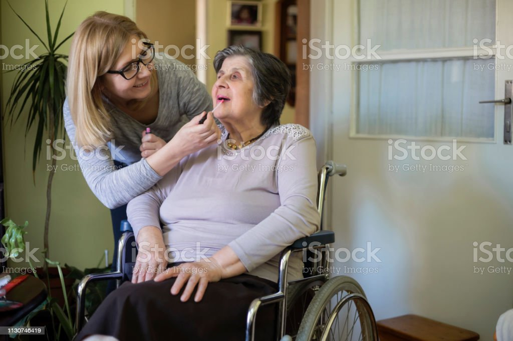 Senior woman in wheelchair have hair styling and make up at home