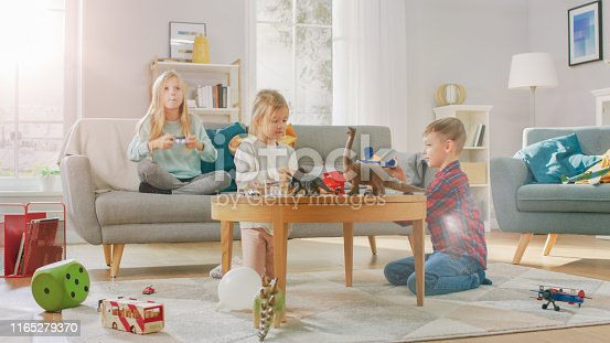 At Home: Cute Girl Playing in Video Game Console, Using Joystick Controller, Her Younger Brothe Plays with Toy Airplane and Youngest Sister Plays with Toy Dinosaurs. Happy Children Playing in the Sunny Living Room.