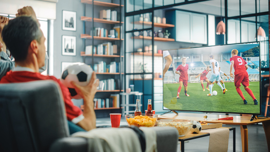 At Home Soccer Fans Sitting on a Couch Watch Football Game on TV, Cheer for Favourtite Sports Team to Win Championship. Screen Shows Professional Football Club Play. Over the Shoulder